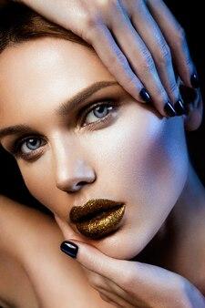 Bella ragazza con glitter oro sul viso