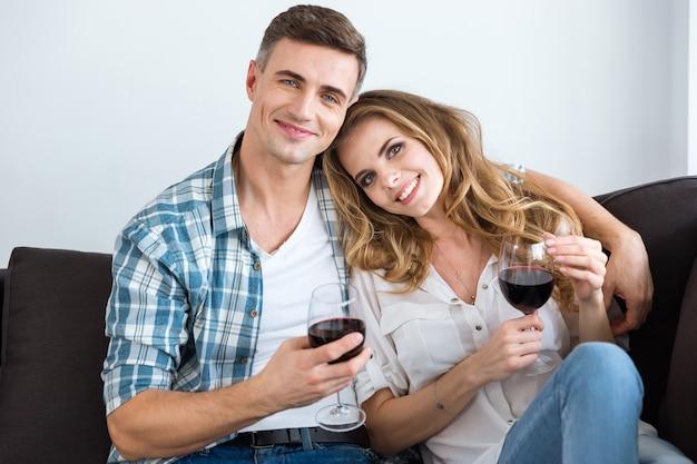Bella coppia seduta sul divano e bevendo vino a casa