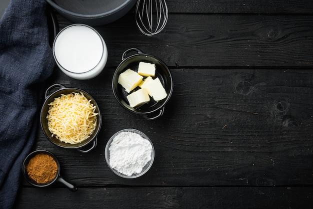 Ingredienti della salsa besciamella sulla vista superiore del tavolo in legno nero