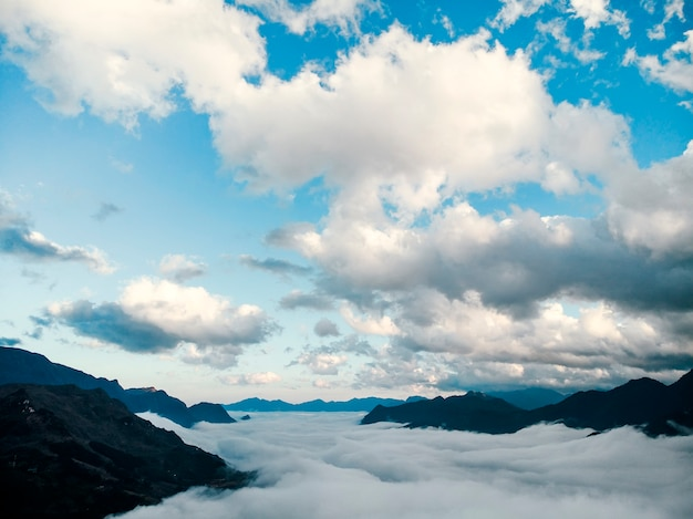 Letto di nebbia e nuvole tra la valle di montagna di sapa, vietnam. montagne tra le nuvole. bellissimo paesaggio con alte montagne, cielo azzurro e nuvole bianche.