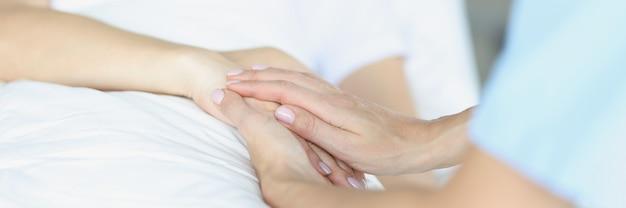 Sul letto giace un medico malato seduto accanto a lui e tiene la mano con simpatia eutanasia in