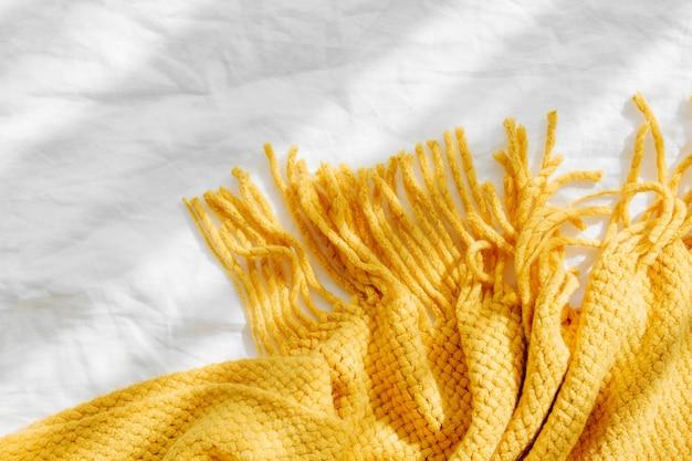 Biancheria da letto con un plaid a maglia giallo. sfondo accogliente con copia spazio. concetto di hygge.