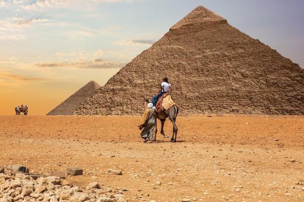 Beduini nel deserto di giza vicino alle grandi piramidi d'egitto.
