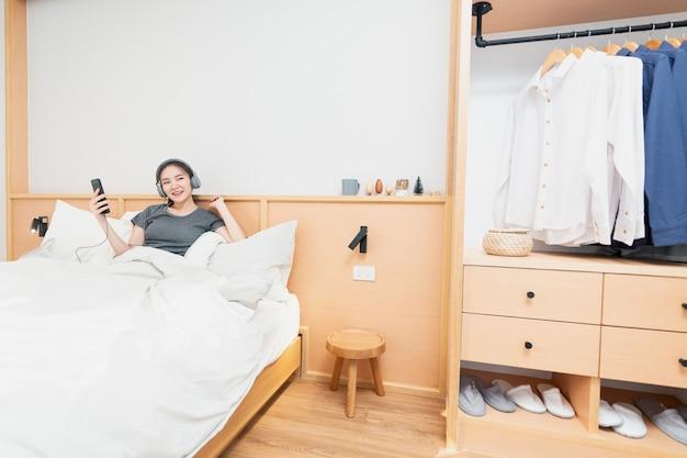 Concetto di camera da letto sul comodo letto una ragazza che ascolta le sue canzoni preferite indossando una cuffia al mattino.