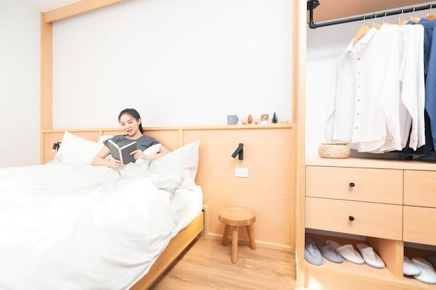 Concetto di camera da letto una ragazza che legge il libro interessante con la coperta bianca che copre il suo corpo che sembra serena e accogliente.