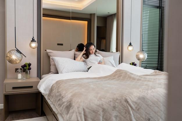 Concetto di camera da letto una ragazza con sensazione di sonnolenza che si sdraia su diversi cuscini grandi e comodi che fissano lo schermo del cellulare per l'aggiornamento delle notizie. Foto Premium