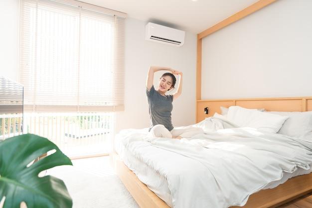 Concetto di camera da letto al mattino la bella ragazza che si sveglia e allunga il suo corpo sul letto di legno marrone.