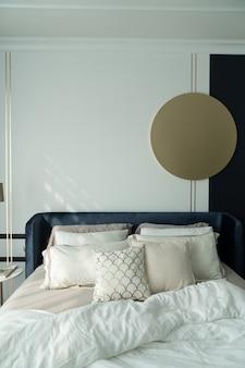 Letto angolare da camera in velluto blu scuro con morbidi cuscini decorati con comodino circolare in marmo e parete in vernice blu navy