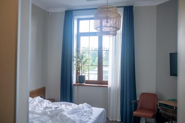 Camera da letto, interno. letto e finestra con tende e pianta d'appartamento in una piccola e accogliente camera da letto in stile minimalista con luce diurna