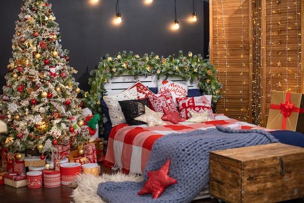 Interno camera da letto nella decorazione scura decorata per natale. il letto con lino blu scuro e molti cuscini è ricoperto da una coperta di lana fatta di filato di pecora hyper large
