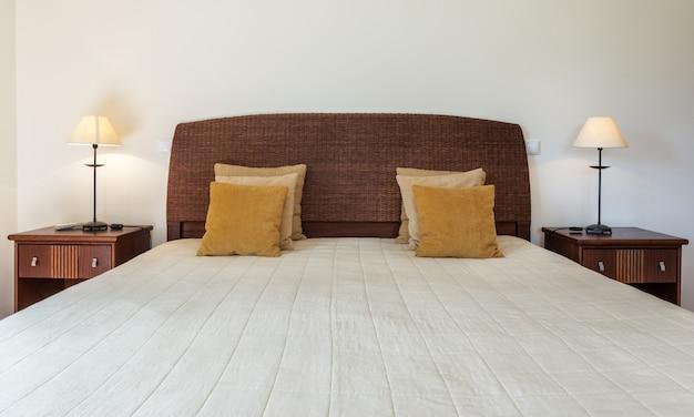Camera da letto in stile moderno con letto e cuscini. vista frontale.