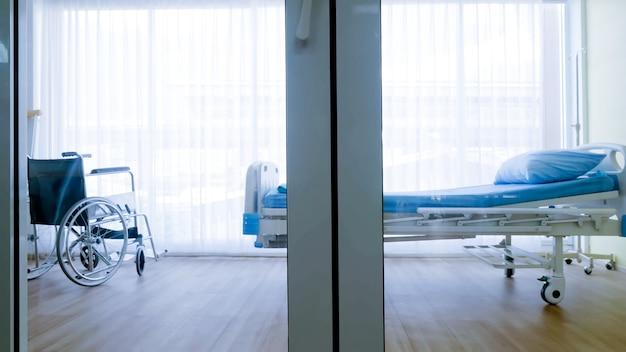 Camera da letto per paziente in ospedale, letto vuoto e sedia a rotelle in reparto ospedaliero.