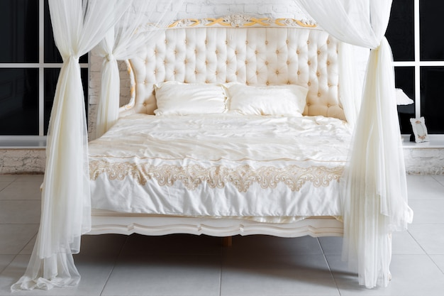 Camera da letto in colori tenui. comodo letto matrimoniale a baldacchino in elegante camera da letto classica. bianco di lusso con interni color oro.