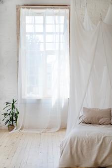 Camera da letto in tenui colori chiari con un pavimento in legno.