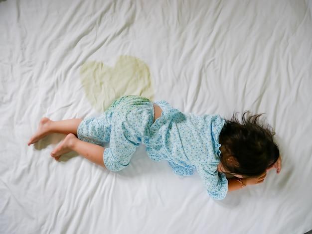 Bedwetting: pepe bambino su un materasso, piedi bambina e pisello in lenzuolo, concetto di sviluppo del bambino, selezionato fuoco a bagnato sul letto