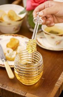 Miele d'api in un contenitore di vetro e mani che tengono la melata su un tavolo apparecchiato in stile vintage