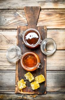 Miele d'api su una vecchia tavola. su uno sfondo di legno.