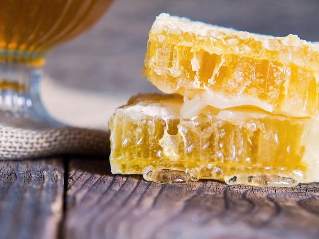 Favo d'ape con il primo piano del miele su un vecchio tavolo di legno