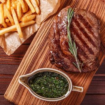 Bistecca di manzo barbecue ribeye con salsa chimichurri e patatine fritte Foto Premium