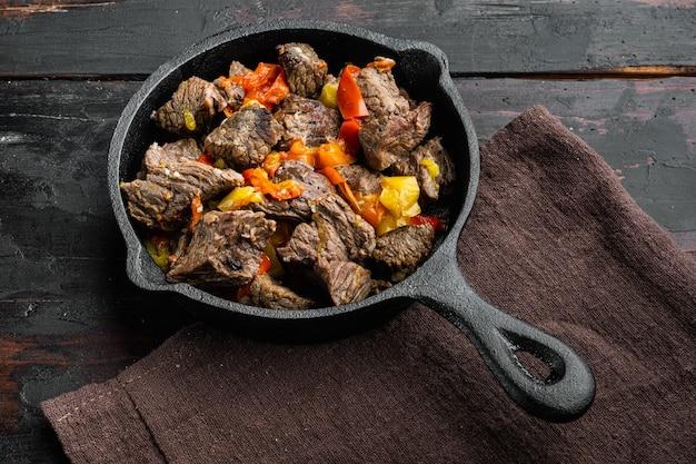 Spezzatino di manzo alla bourguignon con set di verdure, in padella in ghisa, sul vecchio tavolo di legno scuro
