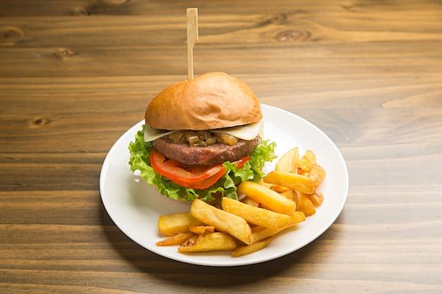 Hamburger di manzo con cipolla caramellata e patatine fritte.
