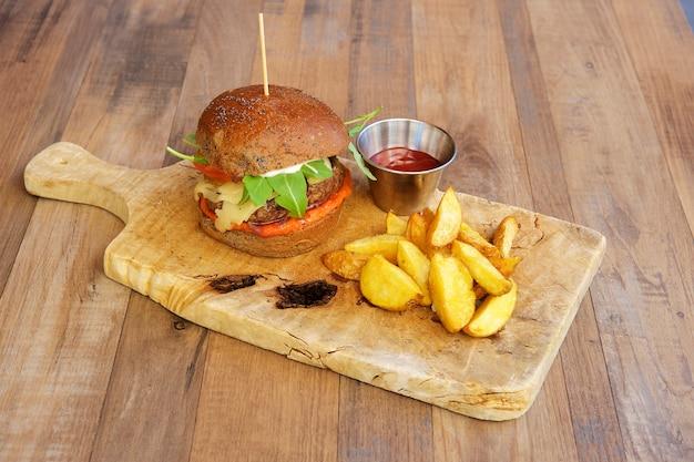 Hamburger di manzo con patate arrosto su fondo in legno.