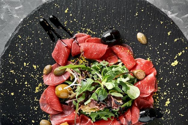 Carpaccio di manzo con rucola su un piatto nero, cucina tradizionale italiana