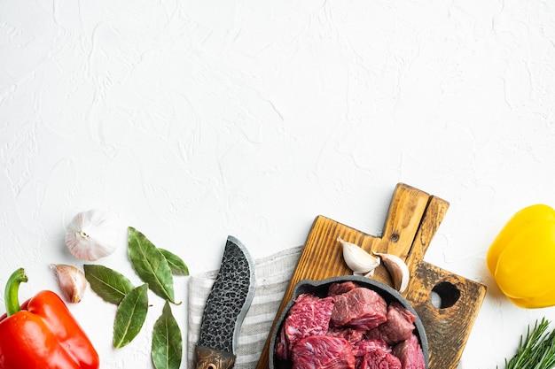 Casseruola di manzo o ingredienti per gulasch impostati, in padella in ghisa, su pietra bianca