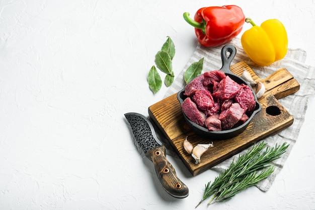 Casseruola di manzo o ingredienti per gulasch con peperone dolce, in padella in ghisa, su superficie di pietra bianca
