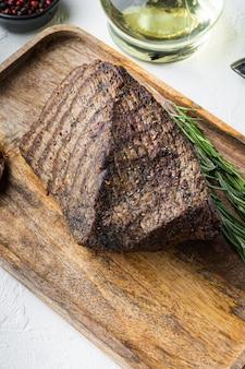 Carni bovine tagliate insieme al forno, sul vassoio di legno, sul tavolo bianco