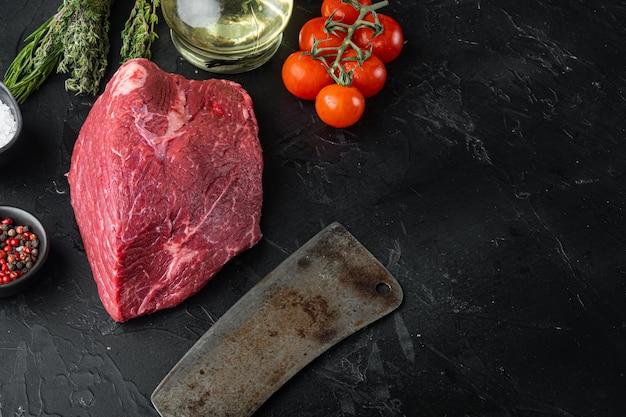 Manzo tagliato insieme crudo con il vecchio coltello da macellaio mannaia, sulla tavola nera