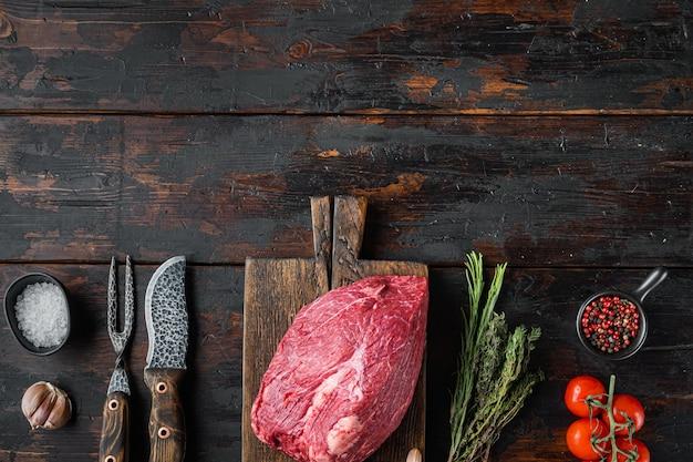 Manzo tagliato insieme crudo, sul tagliere di legno con il vecchio coltello da macellaio mannaia, sul vecchio tavolo in legno scuro, vista dall'alto laici piatta
