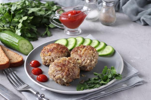 Costolette di manzo servite con cetriolo e salsa di pomodoro su un piatto grigio su sfondo grigio cemento, formato orizzontale