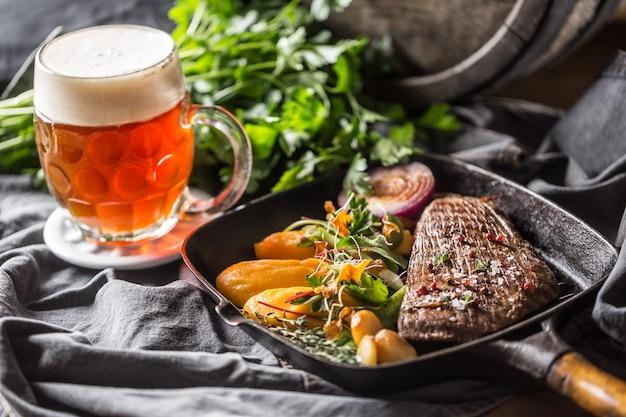 Bistecca di manzo in padella con purea di batata decorazione di erbe all'aglio e birra alla spina.