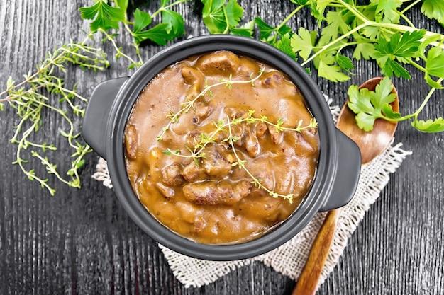 Gulasch di manzo in salsa di pomodoro con rametti di timo in padella su tela, cucchiaio, prezzemolo su fondo di legno dall'alto