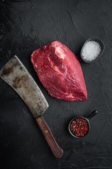 Carne di manzo tagliata cruda insieme con il vecchio coltello da macellaio mannaia, sulla tavola nera, vista dall'alto laici piatta