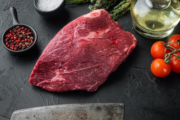 Carne di manzo tagliata cruda insieme con il vecchio coltello da macellaio mannaia, sulla tavola nera