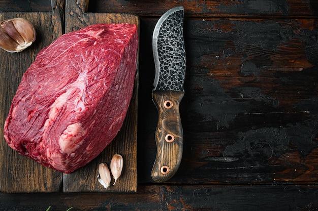 Carne di manzo tagliata insieme crudo, sul tagliere di legno con il vecchio coltello da macellaio mannaia, sul vecchio tavolo in legno scuro, vista dall'alto laici piatta,