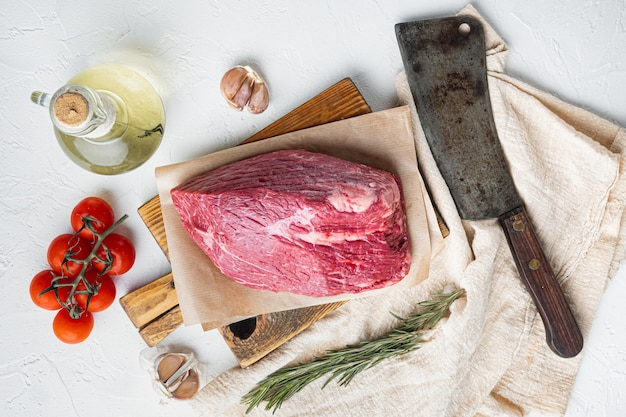 Carne di manzo tagliata insieme crudo, sul tagliere di legno con il vecchio coltello da macellaio mannaia, vista dall'alto laici piatta