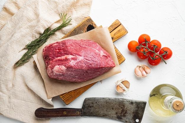 Carne di manzo tagliata cruda, su tagliere di legno con vecchio coltello da macellaio, su tavola bianca