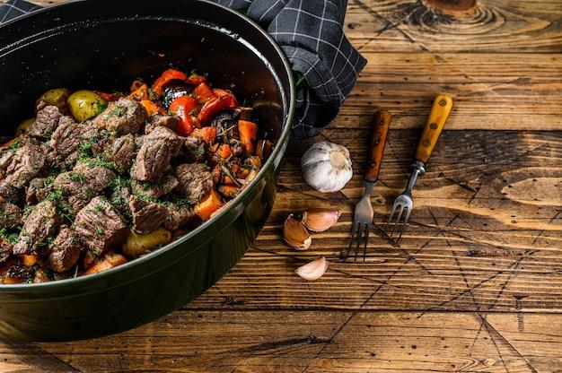 Spezzatino di carne di manzo con patate, carote ed erbe aromatiche. fondo in legno. vista dall'alto. copia spazio.