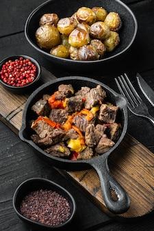 Carne di manzo in umido con patate, carote e spezie insieme, in padella in ghisa, sul tavolo di legno nero