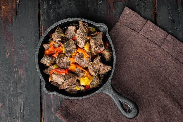 Carne di manzo in umido con patate, carote e set di spezie, in padella in ghisa, su vecchio tavolo di legno scuro, vista dall'alto piatta, con copia spazio per il testo