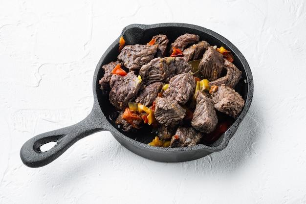 Carne di manzo in umido con patate, carote e spezie set, in padella di ghisa, su superficie di pietra bianca