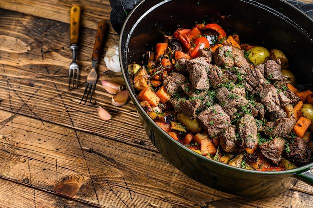 Stufato di carne di manzo e verdure in teglia nera. fondo in legno. vista dall'alto. copia spazio.
