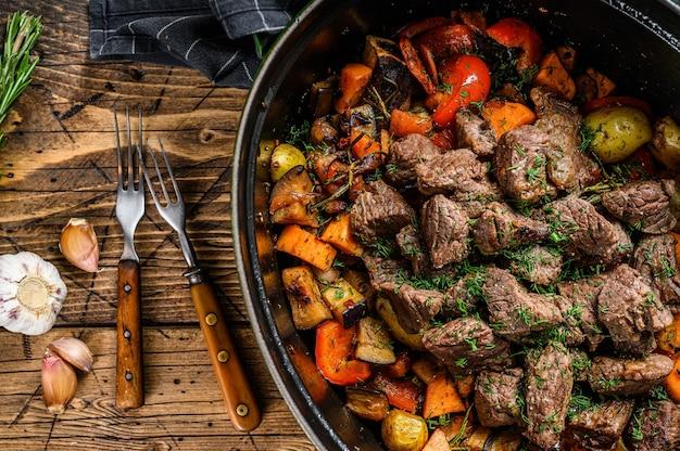 Stufato di carne di manzo e verdure in teglia nera. fondo in legno. vista dall'alto.
