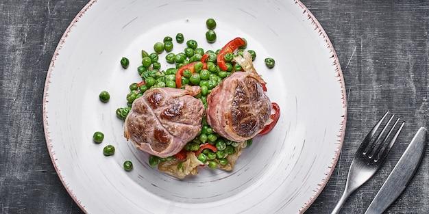 Medaglioni di manzo avvolti in pancetta, servire con piselli e su un piatto su fondo di legno.