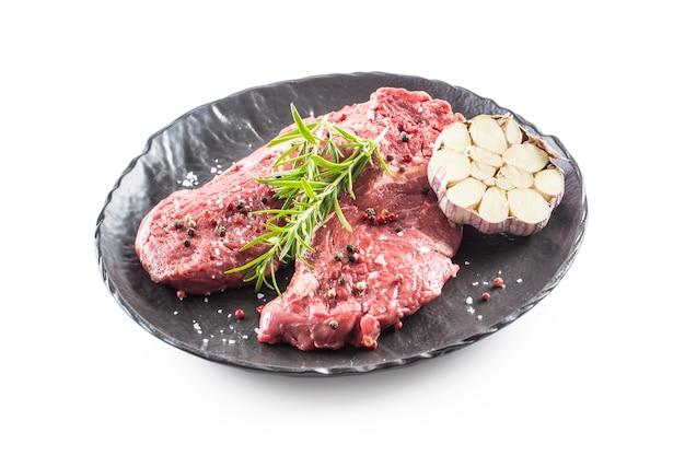Carne di manzo rib-eye con rosmarino sale e pepe in banda nera isolata su bianco.