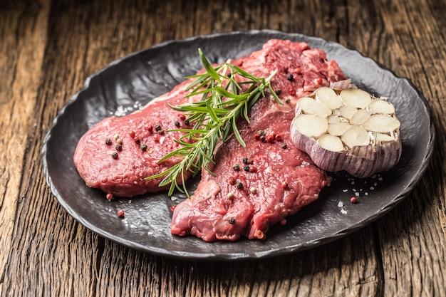 Carne di manzo rib-eye con rosmarino sale e pepe su banda nera.