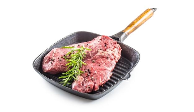 Carne di manzo rib-eye con rosmarino sale e pepe in padella per grigliare isolato su bianco.